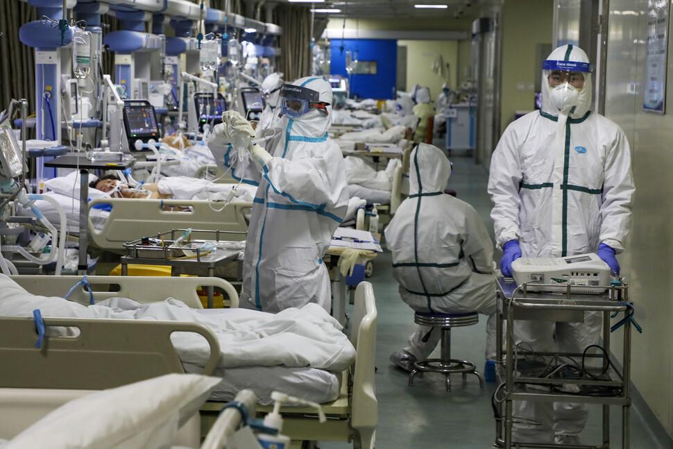 지난 2월6일 코로나19의 발상지로 여겨지는 중국 후베이성 우한의 임시 집중치료시설에서 의료진이 환자들을 돌보고 있다. 우한/AP 연합뉴스