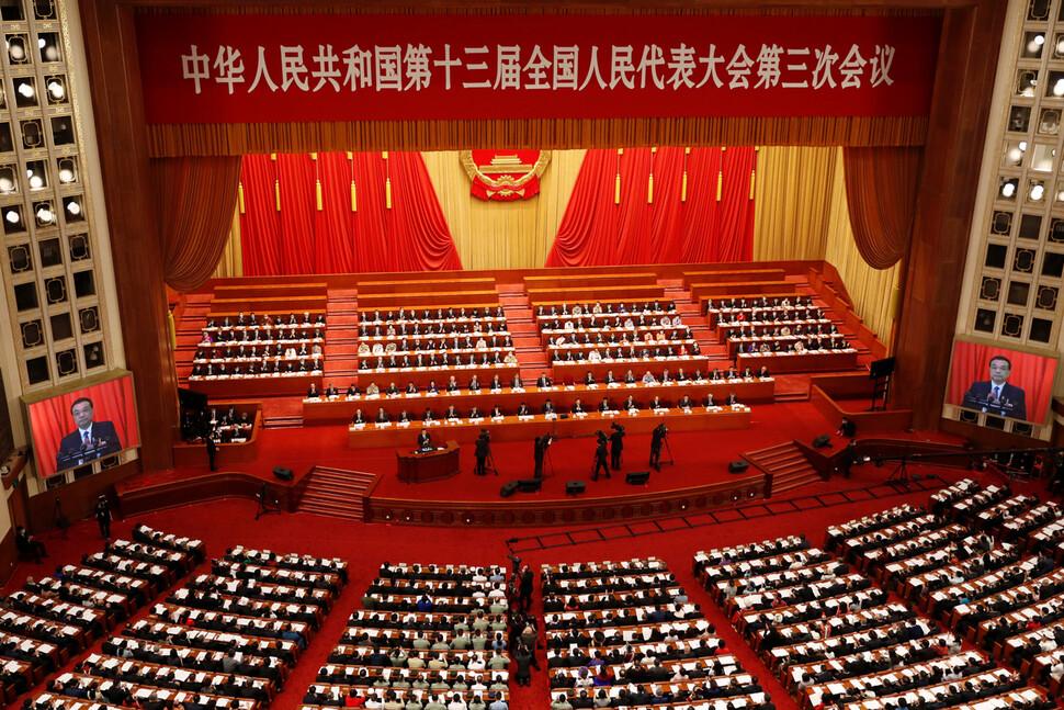 중국 전국인민대표대회(전인대) 제13기 3차 회의가 22일 베이징 인민대회당 만인대회당에서 개막한 가운데, 대회당 양옆 대형 모니터에 리커창 총리가 정부 업무보고를 하는 모습이 보인다. 베이징/로이터 연합뉴스
