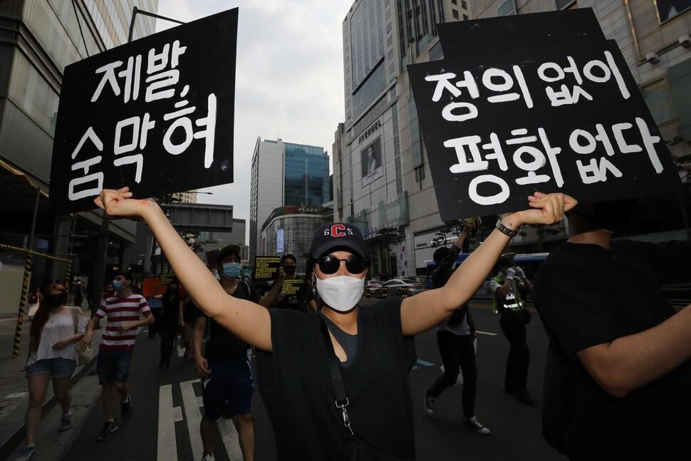 백인 경찰의 과잉 진압으로 숨진 흑인 조지 플로이드씨를 추모하는 행진이 열린 ?6일 오후 서울 명동에서 참가자들이 추모 글귀의 손팻말을 들고 청계천 한빛광장까지 걸어가고 있다. 김봉규 선임기자