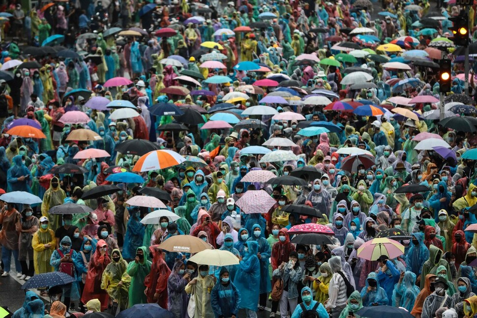 타이 민주화 시위대가 지난 10월18일 방콕 도심의 승전기념비 주변에서 우의를 쓰고 우산을 든 채 집회를 벌이고 있다. 시위대는 정부의 비상칙령을 무시하며 4일째 집회를 강행했다. 연합뉴스