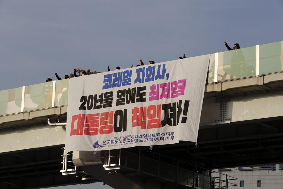 코레일네트웍스 노동자들이 26일 오후 '서울로 7017' 고가 위에서 임금 인상 등 처우 개선을 요구하는 대형펼침막을 내걸고 기습시위를 벌이고 있다. 김명진 기자
