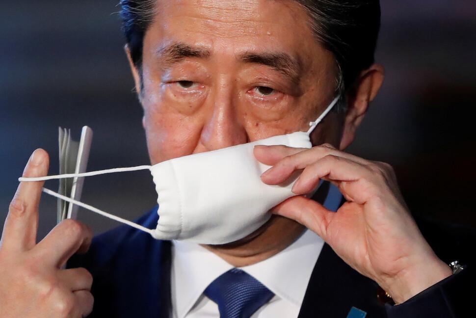 아베 신조 일본 총리가 6일 오후 도쿄 총리관저에서 코로나19 긴급사태 선언과 관련한 설명을 하기 위해 마스크를 벗고 있다. 도쿄/로이터 연합뉴스