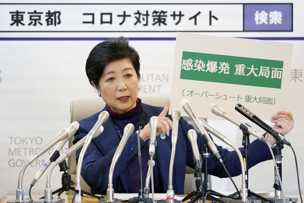 """고이케 유리코 일본 도쿄도지사가 25일 저녁 긴급 기자회견을 열어 """"감염 폭발 중대 국면""""이라고 쓴 팻말을 들어 보이고 있다. 도쿄/EPA 연합뉴스"""