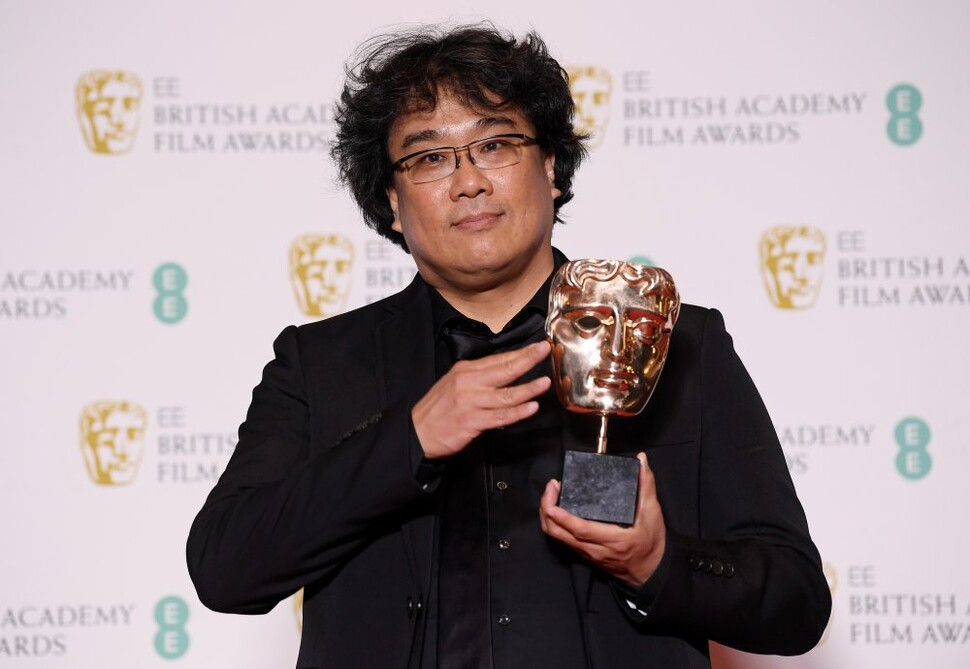봉준호 감독이 2일(현지시간) 영국 런던 로열 앨버트 홀에서 열린 영국영화TV예술아카데미(BAFTA) 시상식에서 영화 ''기생충''으로 외국어영화상을 받은 뒤 상과 함께 포즈를 취하고 있다. 런던 로이터/연합뉴스