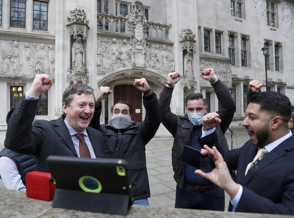 우버 기사들이 19일 영국 런던 대법원 밖에서 우버 기사가 노동자라는 대법원 판결이 나왔다는 소식을 태블릿을 통해 접하고 기뻐하고 있다. 런던/AP 연합뉴스