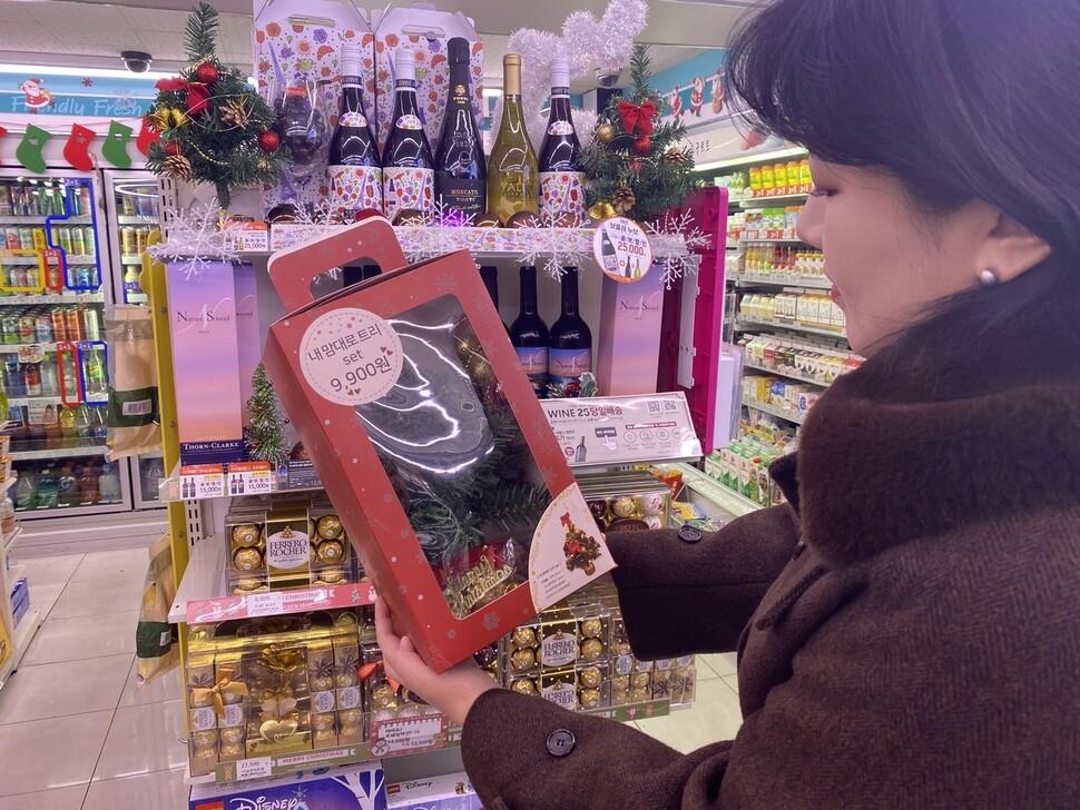 지난 18일 서울의 한 편의점에서 한 여성이 간단히 집에 성탄절 트리를 만들 수 있는 1인 가구용 크리스마스 상품 '내 맘대로 트리 세트'(지에스25)를 집어 들고 있다. 지에스리테일 제공