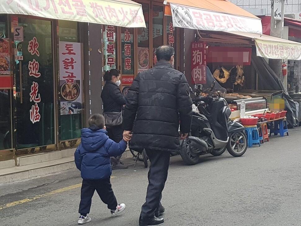 28일 서울 영등포구 대림동에 있는 대림중앙시장. 한 남성이 마스크를 착용한 아이의 손을 잡고 걸어가고 있다.