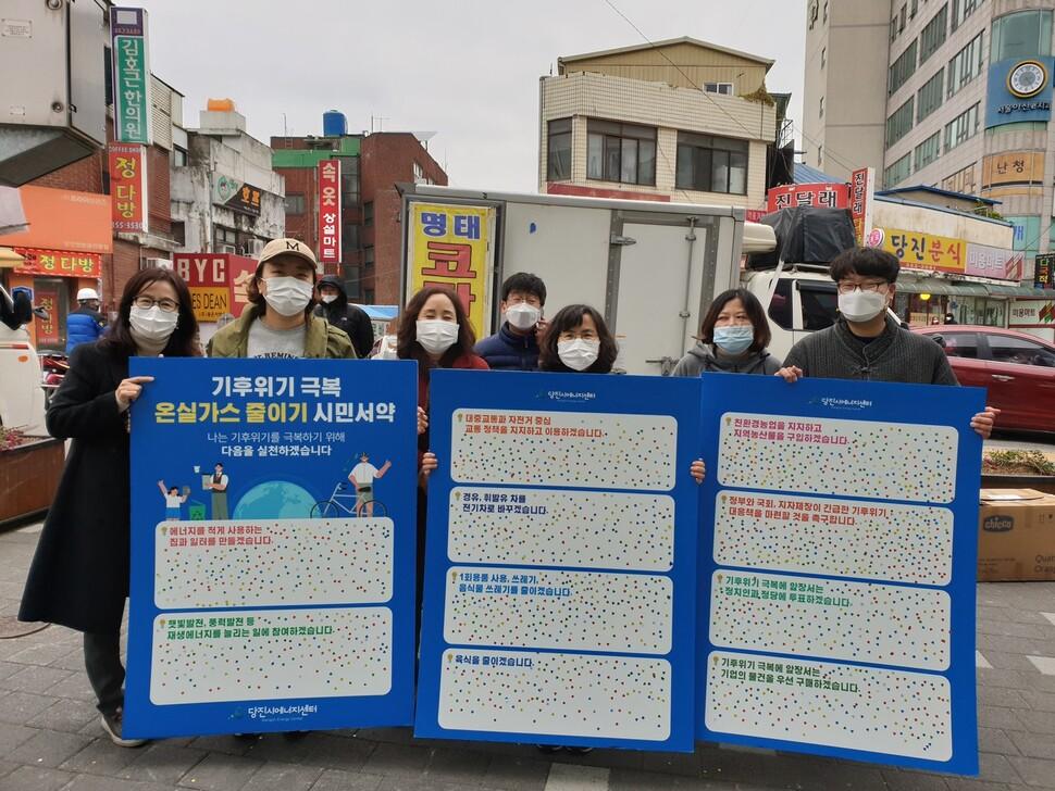 지난달 20일 충남 당진의 한 전통시장 입구에서 당진시에너지센터가 온실가스 줄이기 시민서약 캠페인을 벌이고 있다. 당진시에너지센터 제공