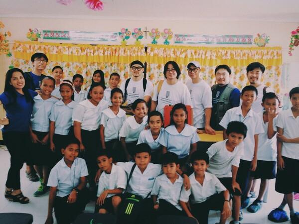 강제욱(맨뒷줄 오른쪽 둘째) 사진가는 2015년 '예술과 재난' 프로젝트팀을 이끌고 필리핀 타클로반의 산 페르난도 센트럴 스쿨을 방문해 태풍으로 망가진 아이들의 장난감을 3D 프린터로 복원했다. 강제욱 사진가 제공