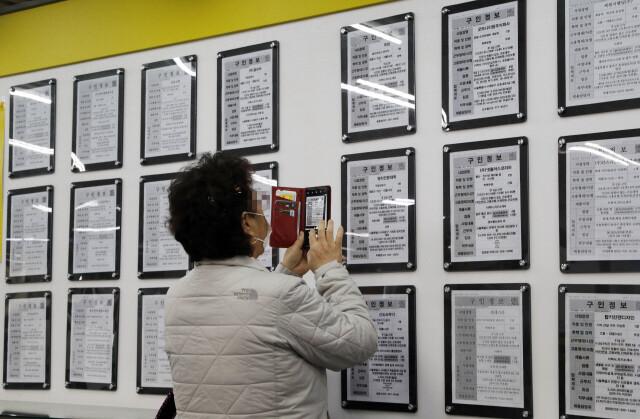 지난달 14일 오후 서울 마포구 서부고용복지플러스센터에서 한 시민이 구인 게시물을 휴대전화로 찍고 있다. 김혜윤 기자